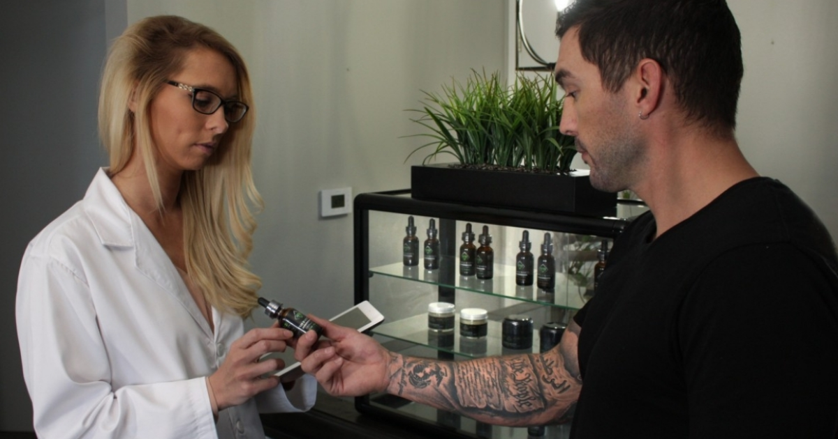 A man hands a CBD bottle to a woman in a lab coat