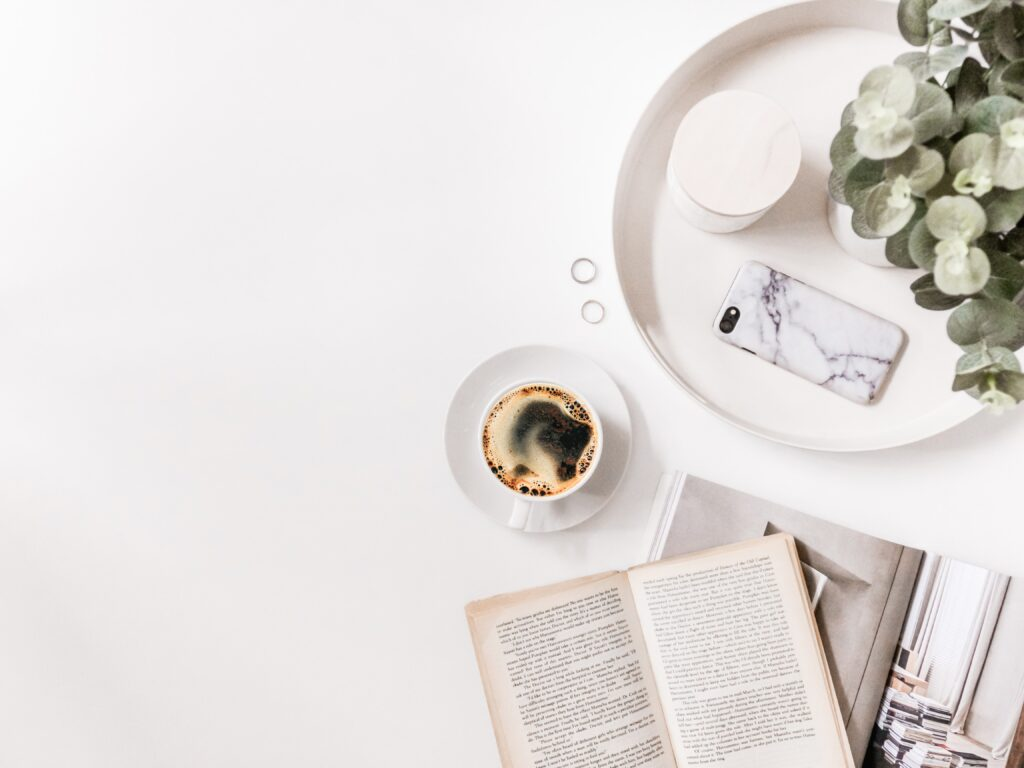 A cup of coffee near books and magazines on a white background