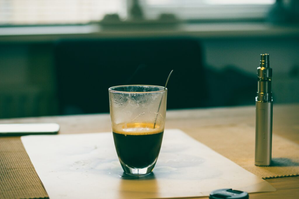 A vape device next to a small shot of coffee in a glass container with a spoon in it.