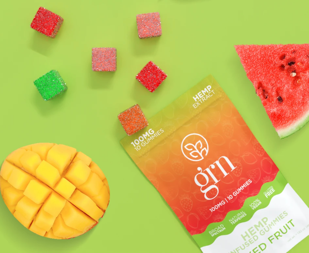 A packet of GRN CBD sweets on its side, open to reveal cubes of gummies. Slices of fruits are also beside the packet on a lime green background