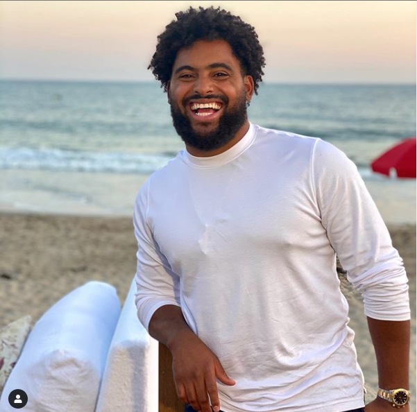 male cbd business owner, nico marley, stood in a white shirt on a beach