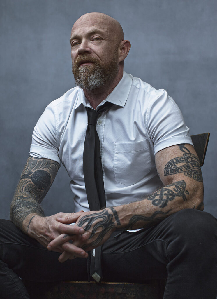 A man dressed in black and white,  bearing tattoos on his arms, is photographed while seated.