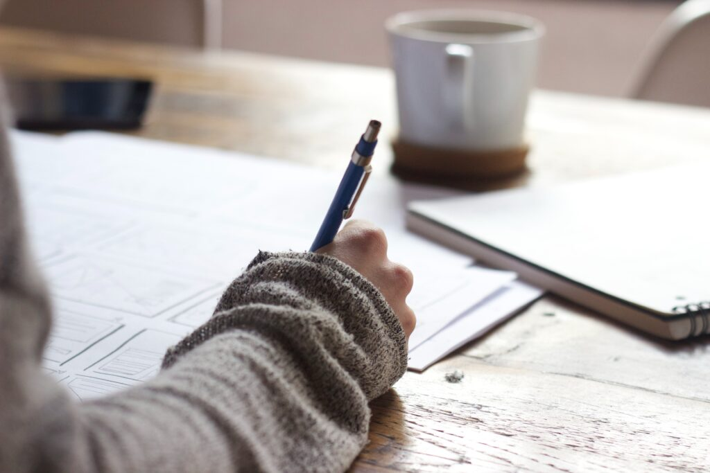 Notes and papers across a desk where someone is studying about medical cannabis. Their arm cuts across the notes holding a pen. A cup of coffee sits almost out of view