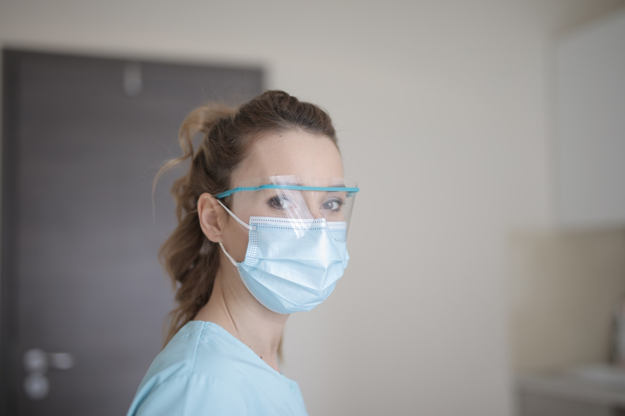 Woman wearing blue face mask and hospital scrubs looks at the camera