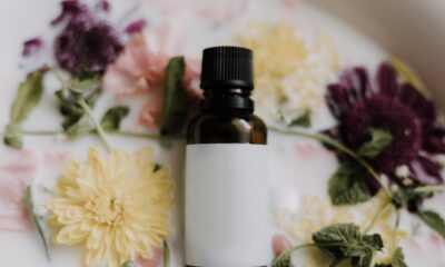 A small bottle of oil on a bed of flowers