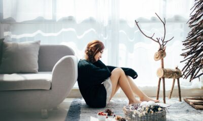 A woman sitting on the floor surrounded by christmas decorations