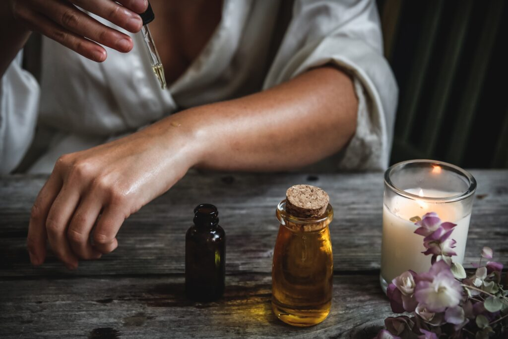 A woman applying CBD oil to her arm while a candle burns to the lower left of the photo. There are purple flowers on the right hand side on a wooden table.