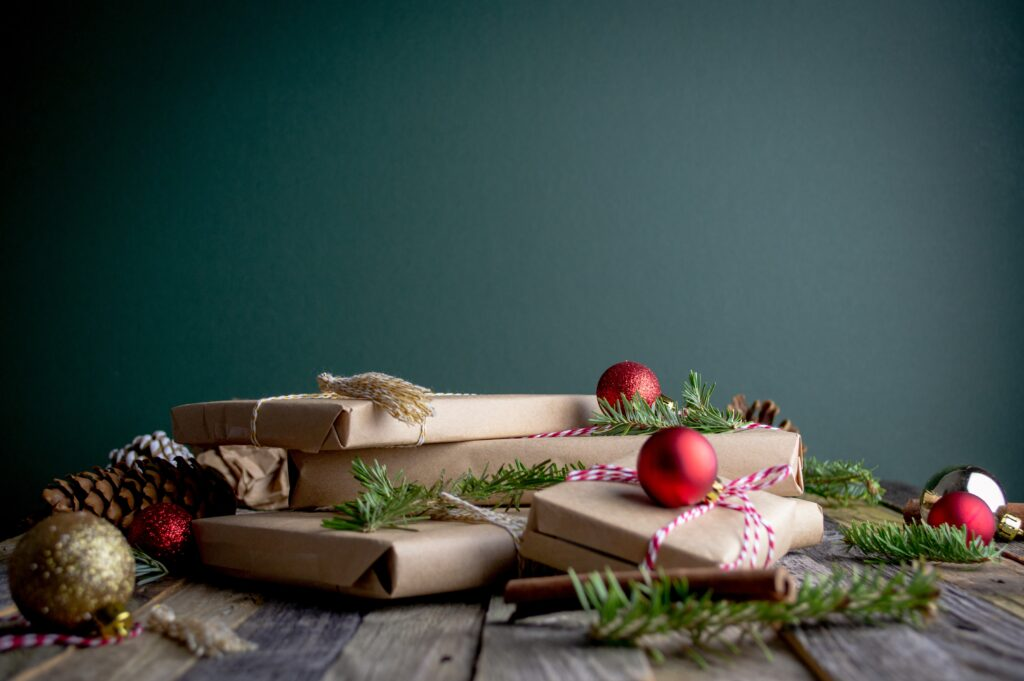 A pile of brown paper wrapped presents on the floor with baubles against a dark wooden background.