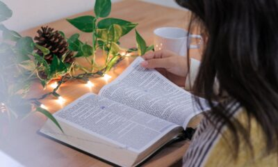 A woman studying a book with fairy lights
