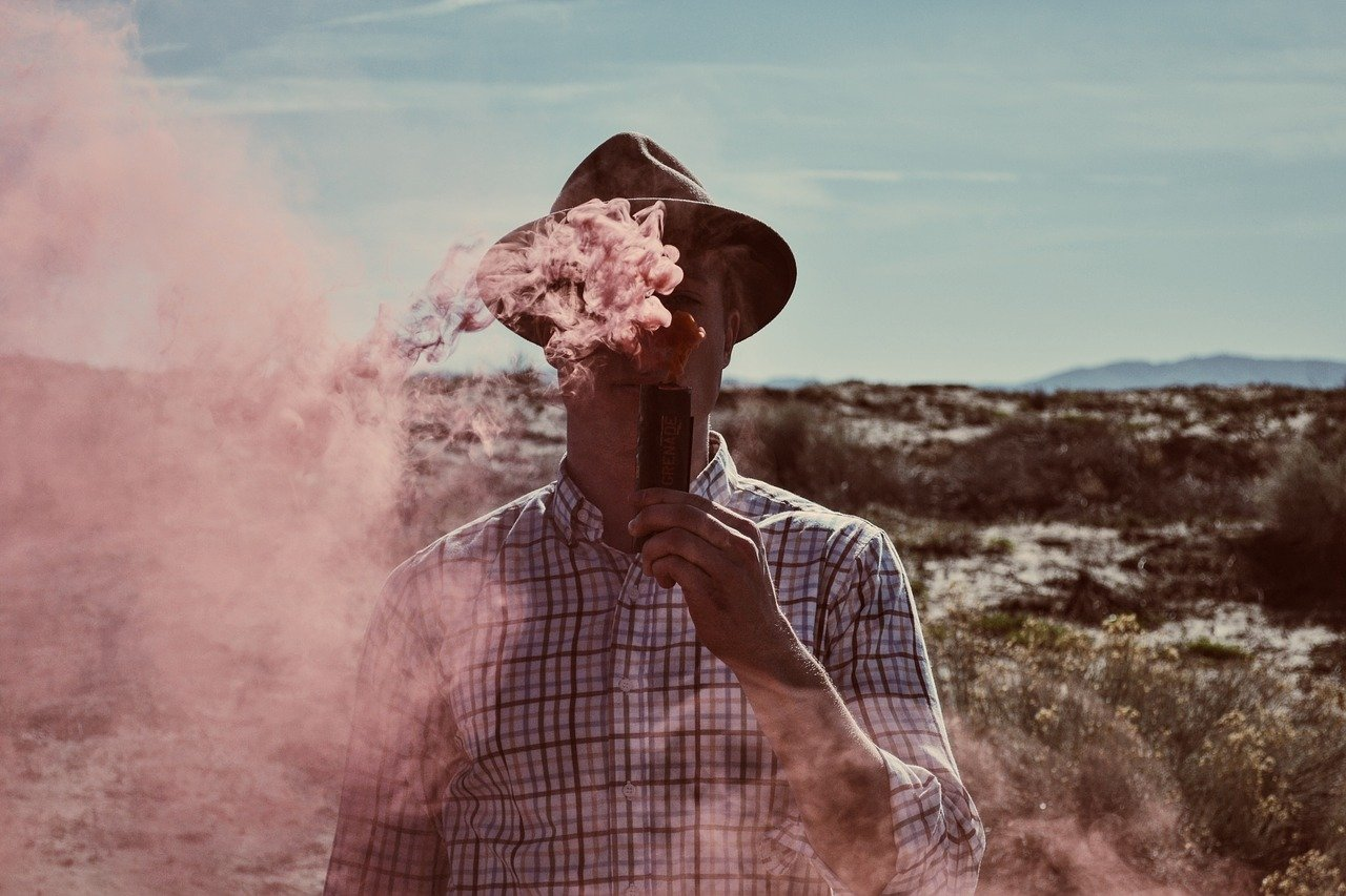 Man in checked shirt vaping outdoors