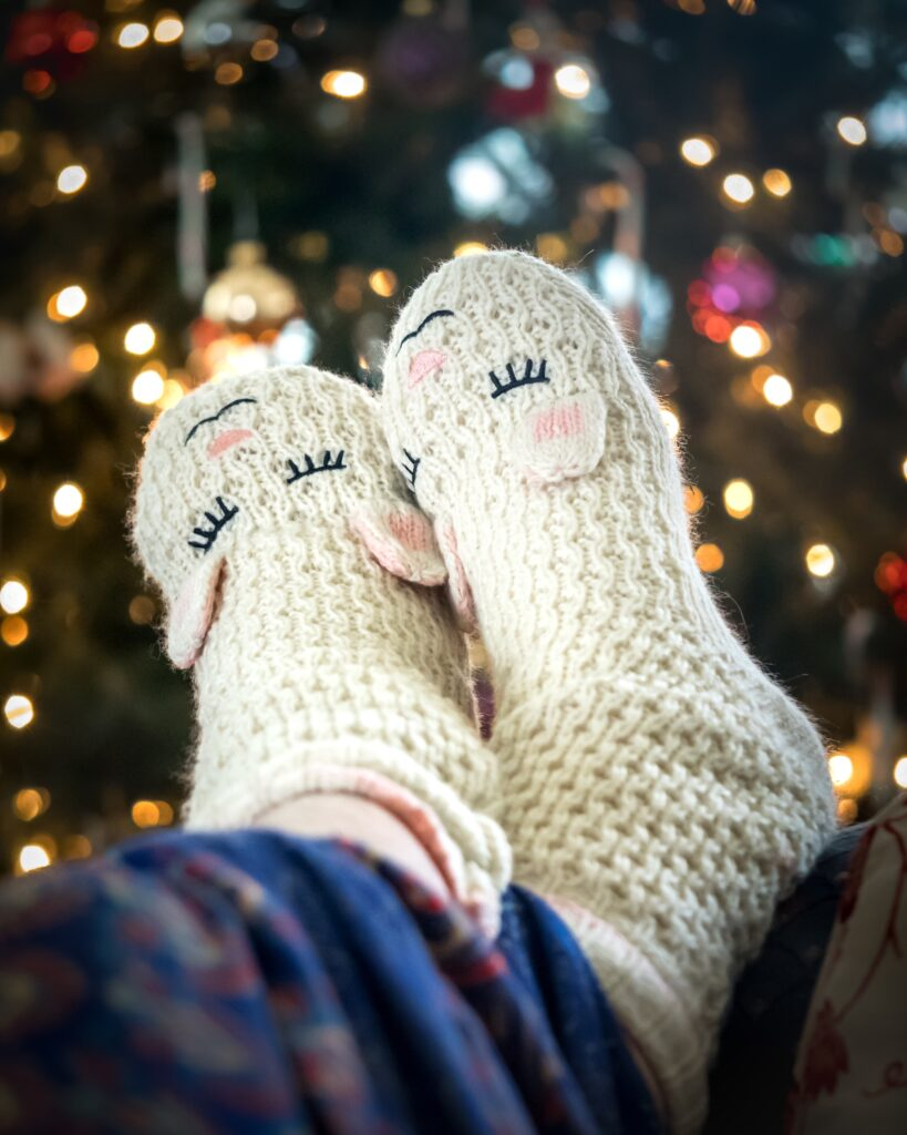 Two feet resting on a sofa with knitted sheep socks on. There is a twinkly xmas tree the background shining.