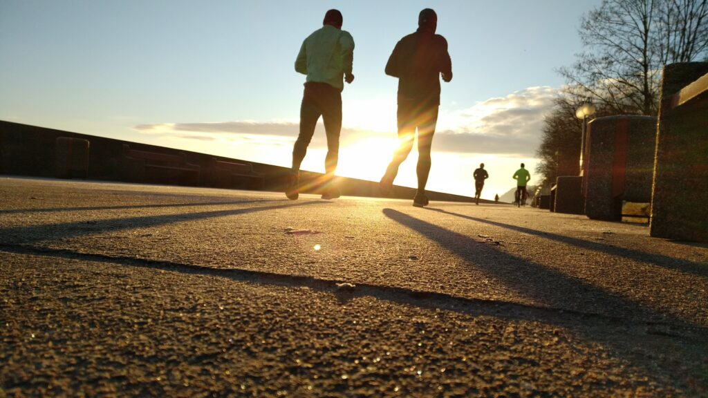 A series of runners against a bright sun on a pavement.