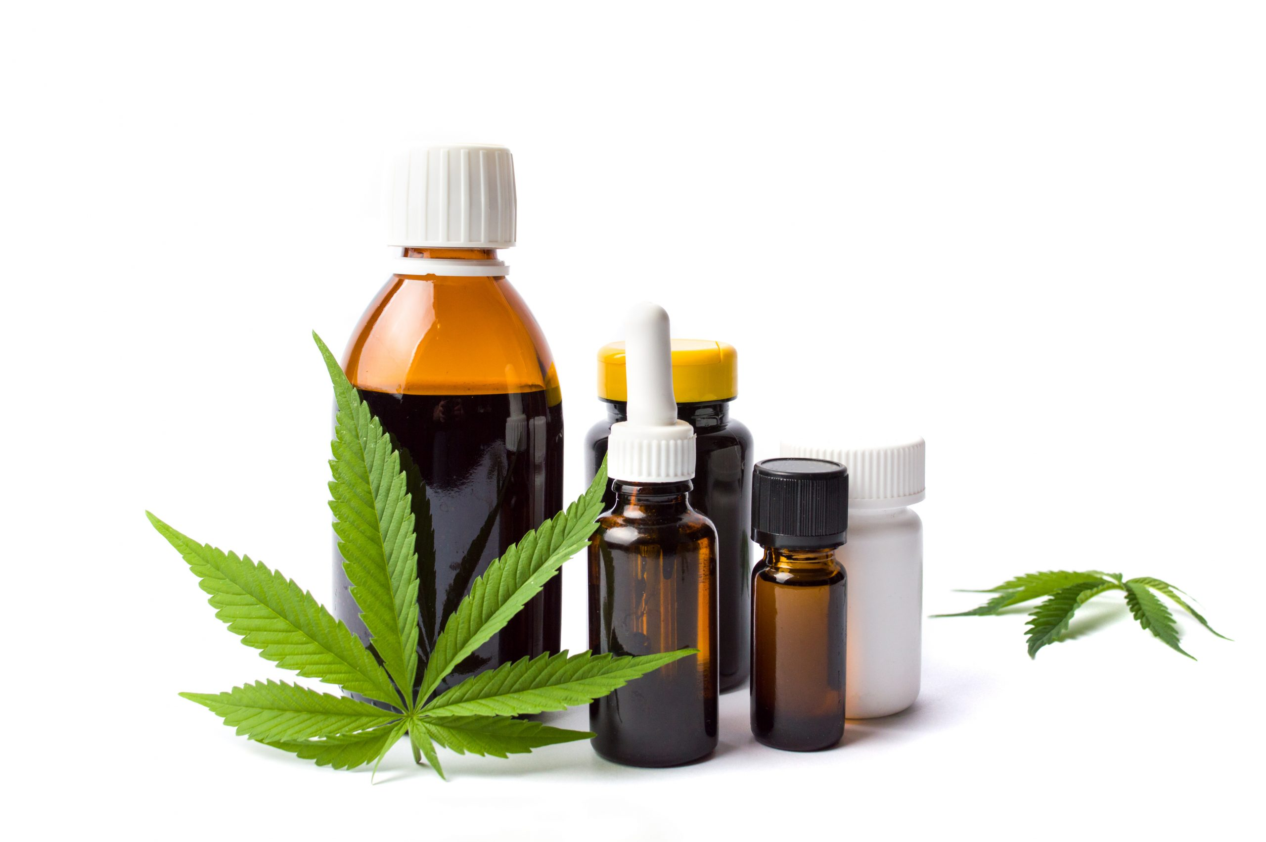 A green cannabis leaf is stood against a brown medicine bottle