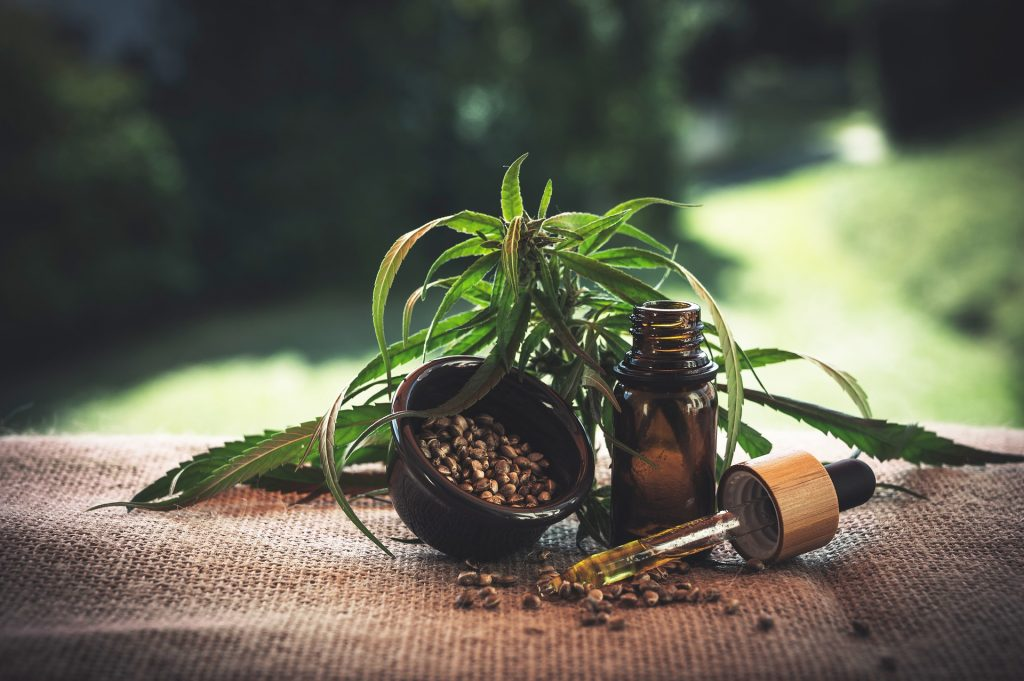 A brown bottle of oil sits on a hemp blanket with a cannabis leaf on top. There is a small brown bowl of hemp seeds to the left and a dropper containing on oil on the right