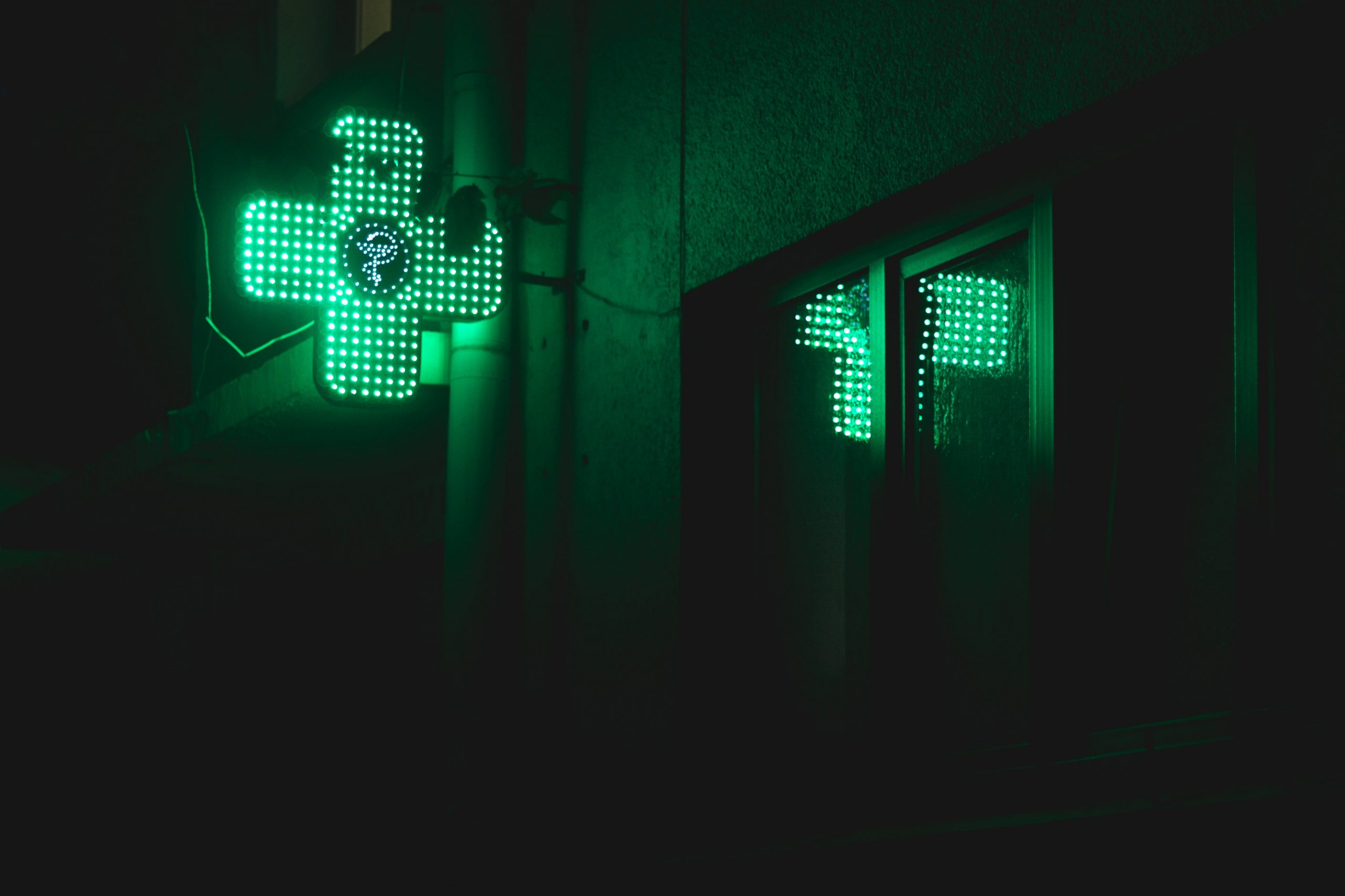 green pharmacy symbol in the shape of a cross is alight on a dark night