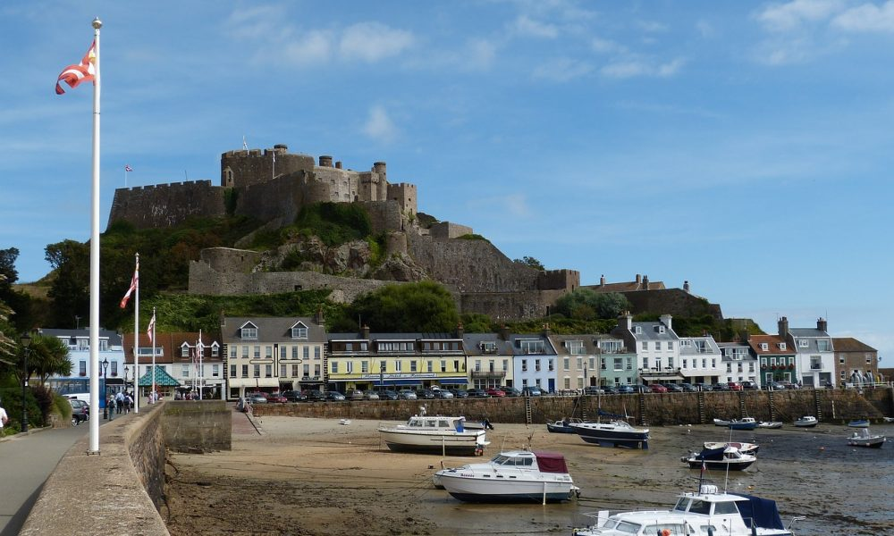 A stone castle sits atop a hill overlooking a harbour in Jersey