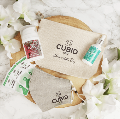 Hand sanitiser sachets, a grey face mask and two CBD wellness products photographed on a wooden plank decorated with while flowers