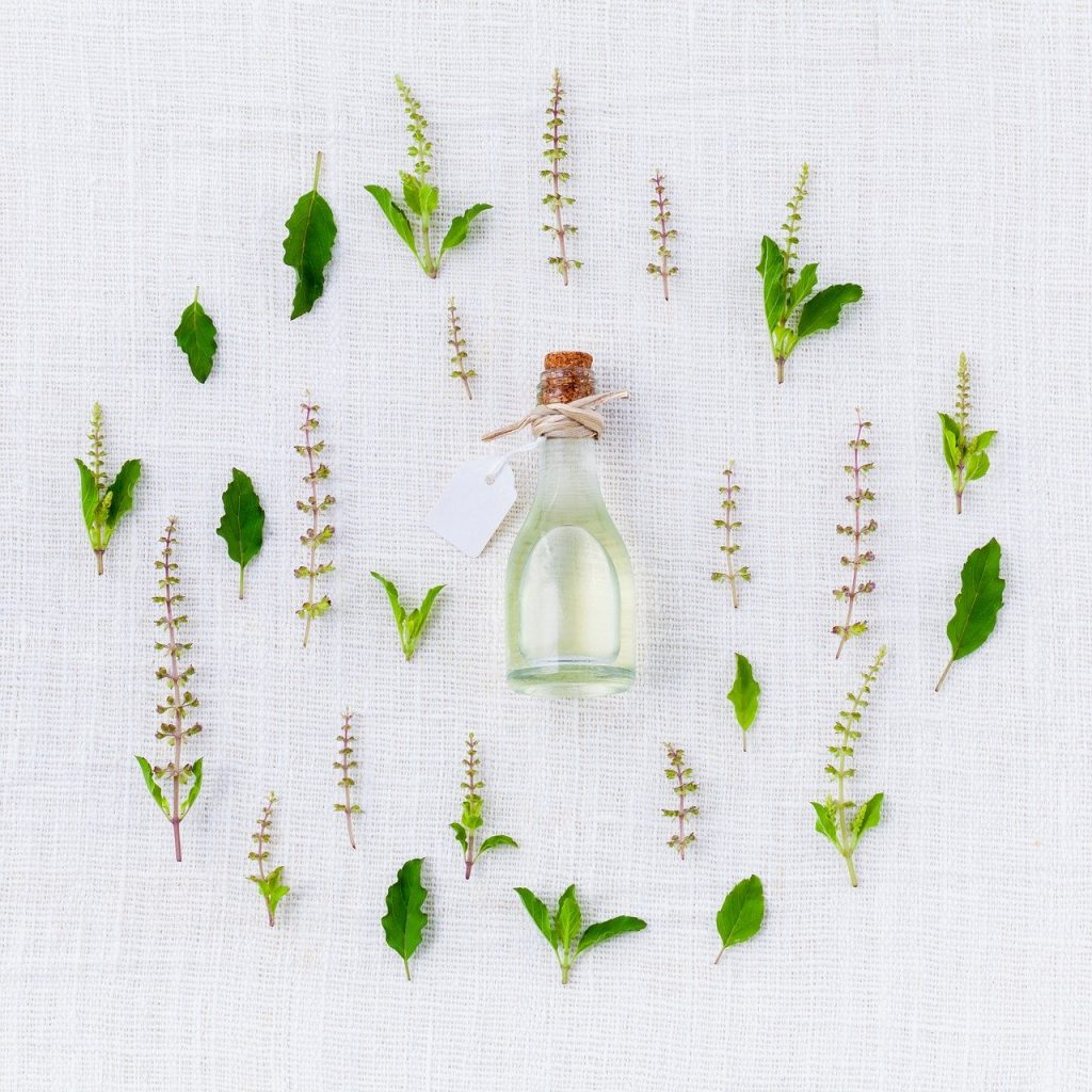 A collection of herbs, leaves and flowers on a white background surrounding a small bottle of oil with a wooden stopper. There is a string bow around the neck of the bottle.