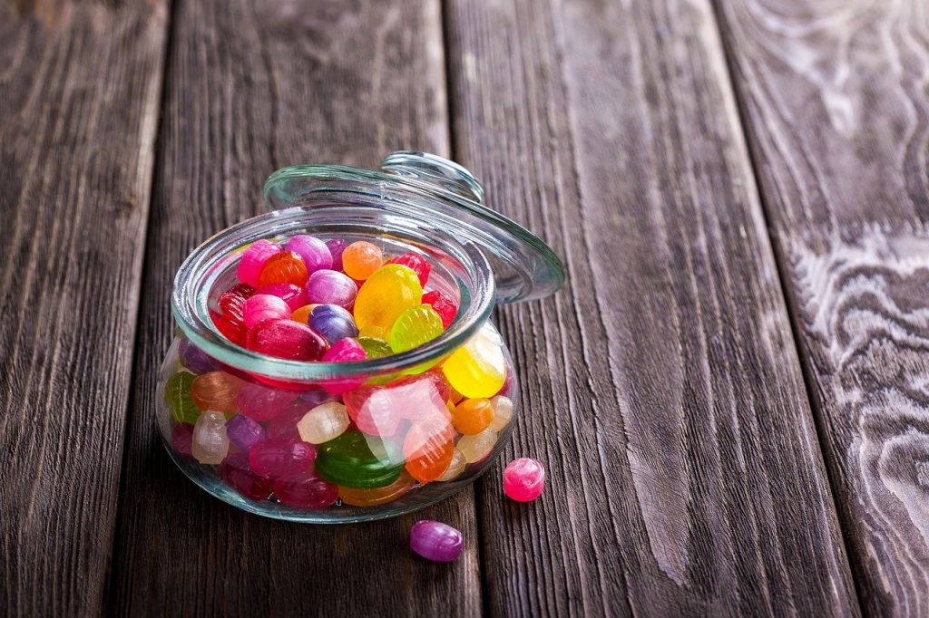A small jar of brightly coloured sweets on a wooden surface