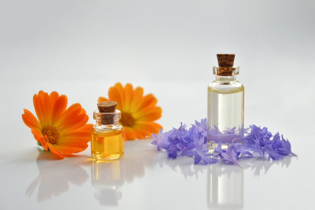 Two small bottles of cbn oil are on a white background surrounded by flowers