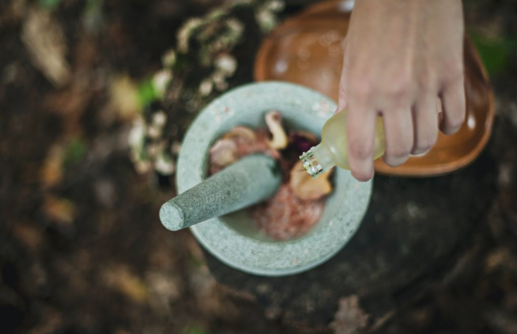 A hand pouring oil into a bowl filled with flowers