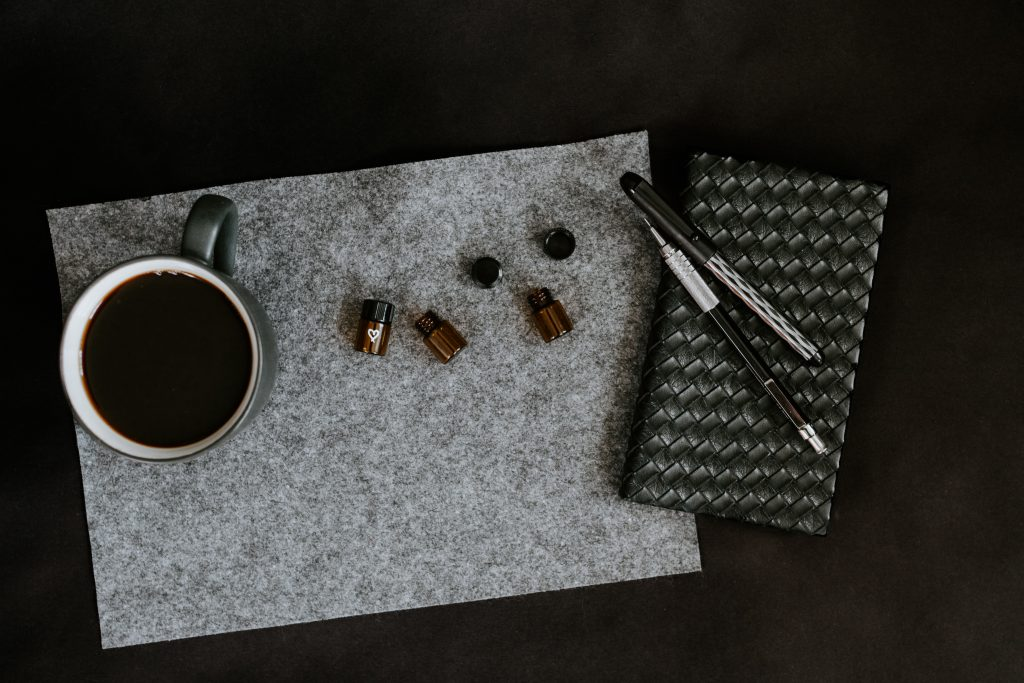 A black background that has. a vape pen, a diary, a coffee cup and small oil bottle on it
