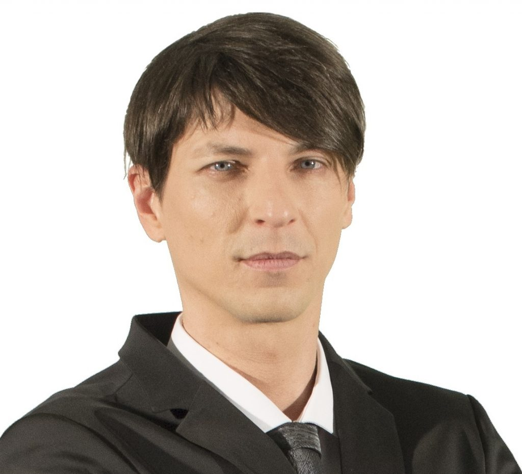 A man with black hair wearing a black suit and tie posts for a photograph