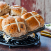 Hot Cross Buns on a plate with some butter.