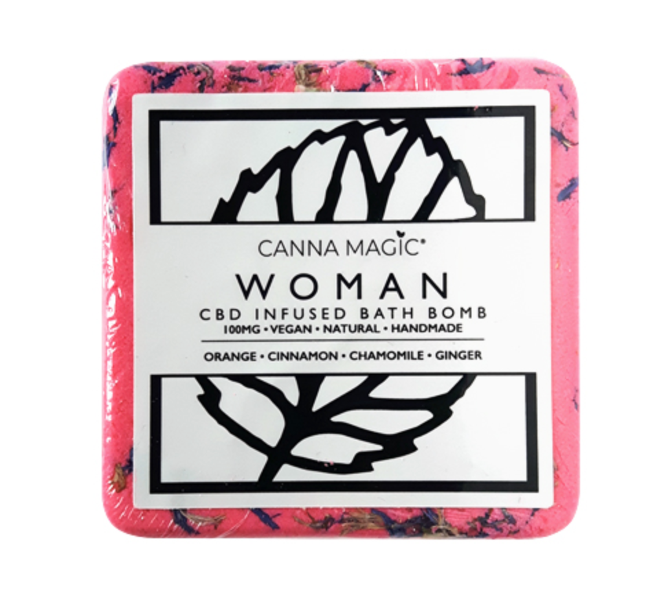 A pink square bath bomb with a black and white label on the front saying woman.