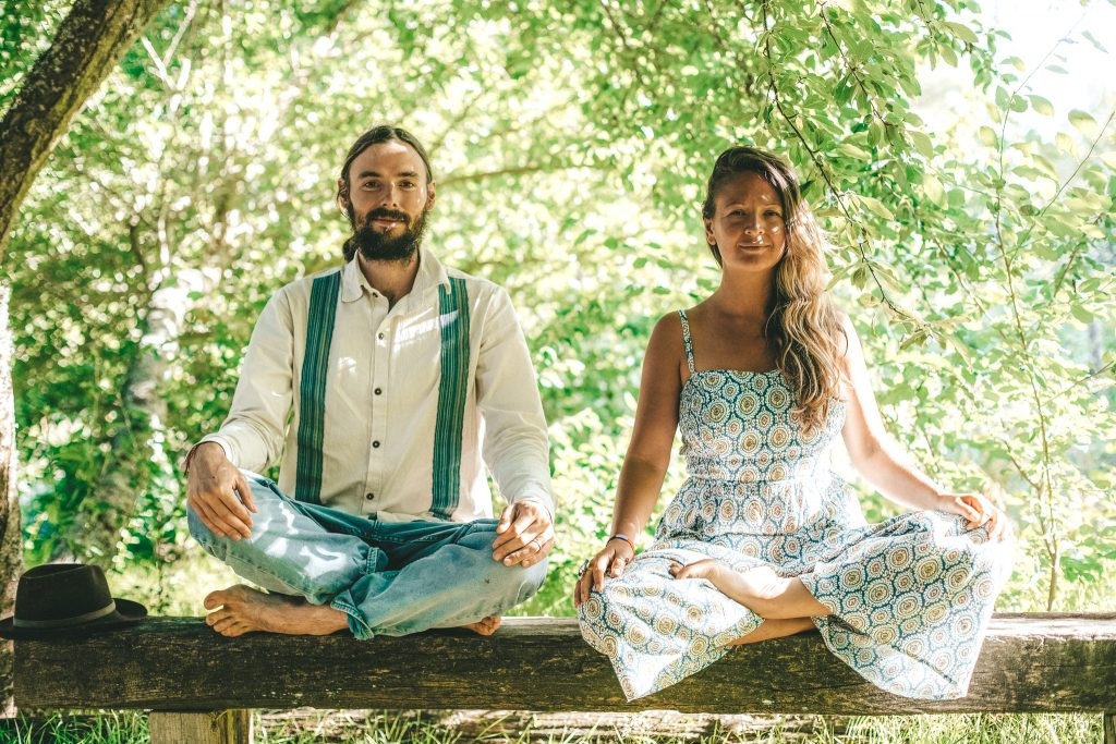 A man and woman sit cross-legged in front of greenery
