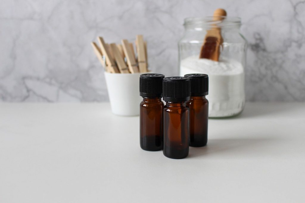 Three brown bottles of CBD oil on the white counter top in a kitchen with a container of flour in the background.