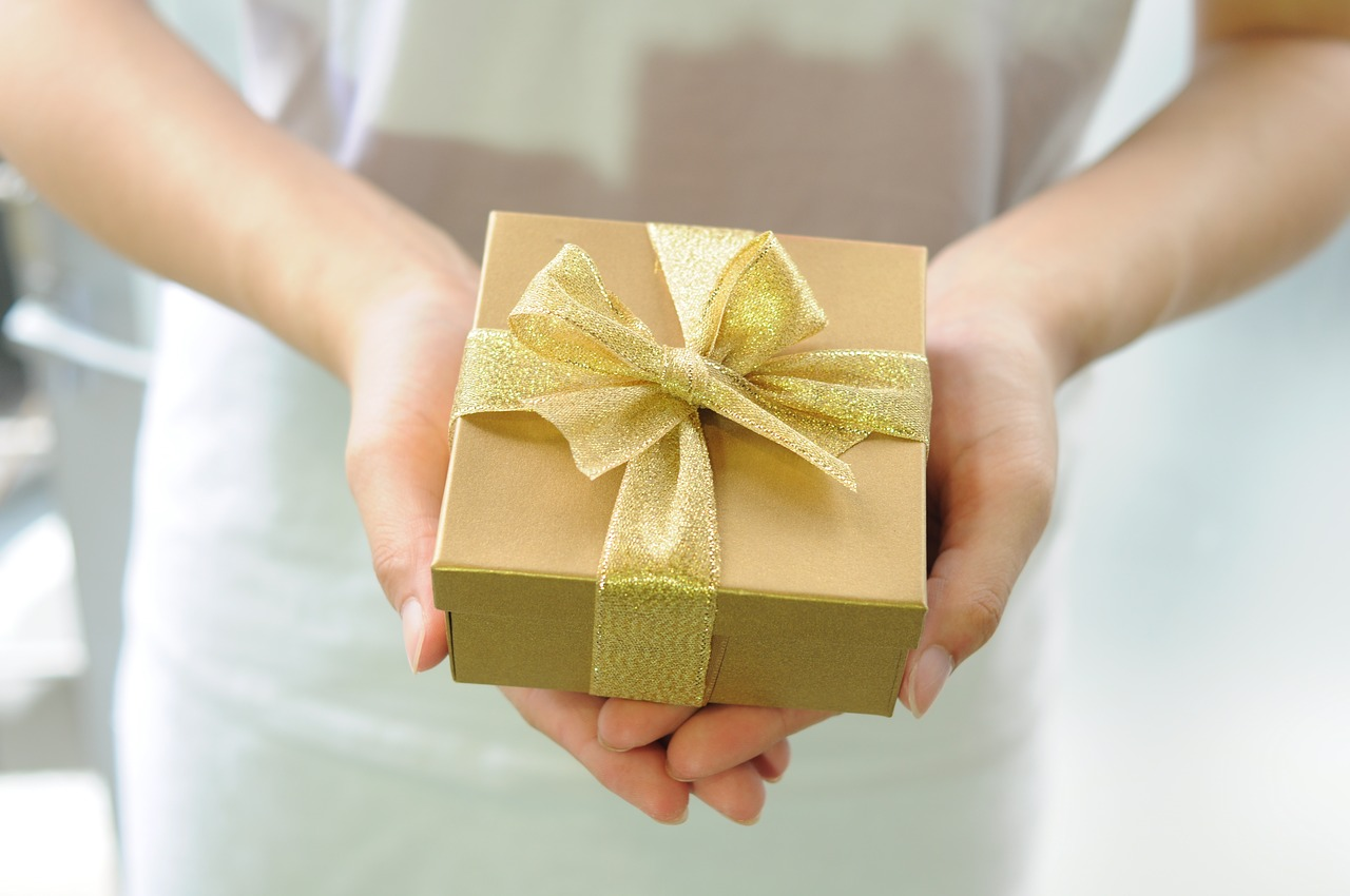 A woman's hands holding a gold gift box for Mother's Day with a gold ribbon on it.
