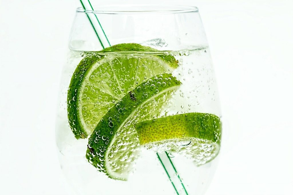 A clear glass of gin and tonic with a straw and three slices of limes in it