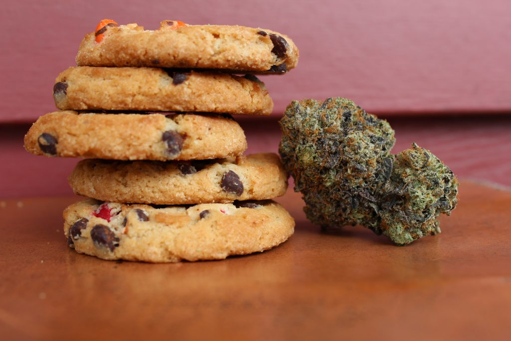 A stack of chocolate chip cookies on a wooden counter with CBD buds beside them.