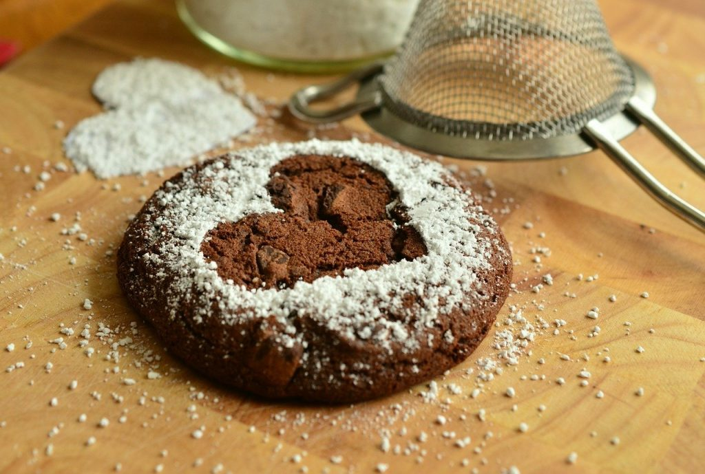 A chocolate brownie on the desk with a heart cut out of white sieved flour on top. The sieve is also lying to one side of the edible.