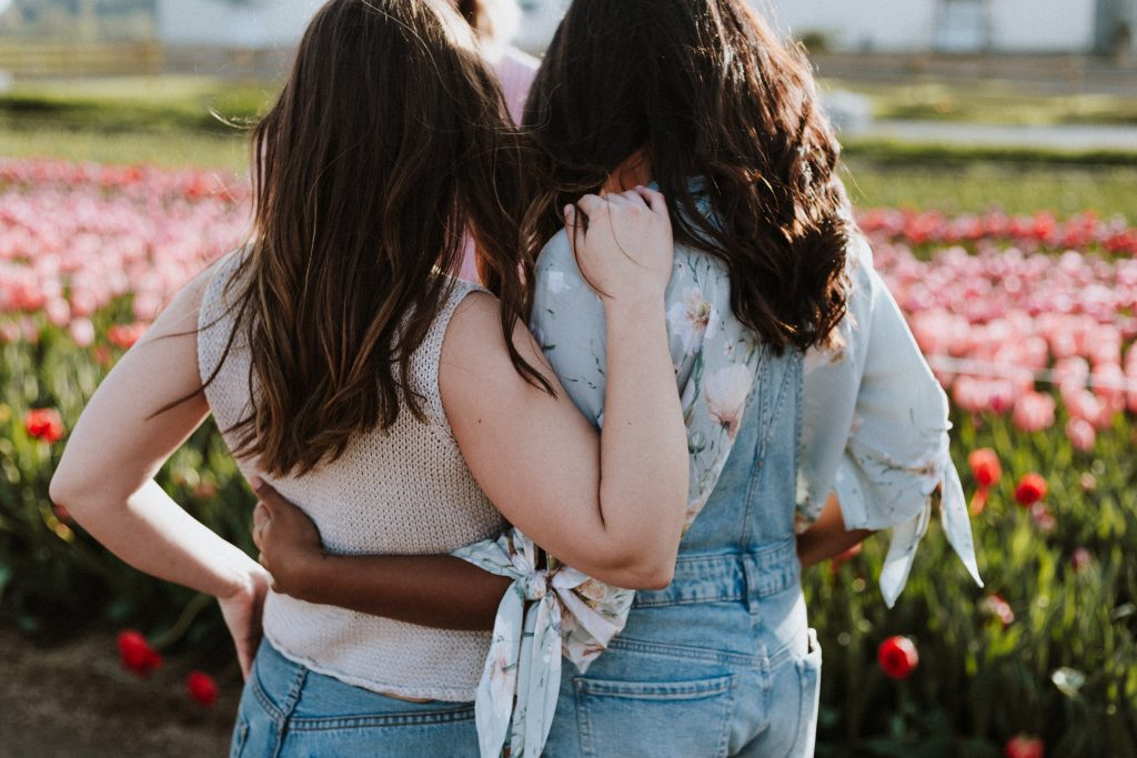 Two women with the back to the camera hug while facing a field of pink flowers