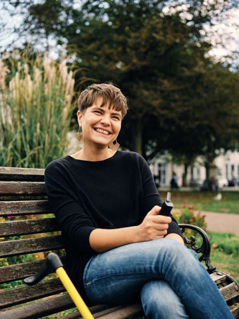 A woman sitting on a park bench smiling and holding a cannabis vaping device.