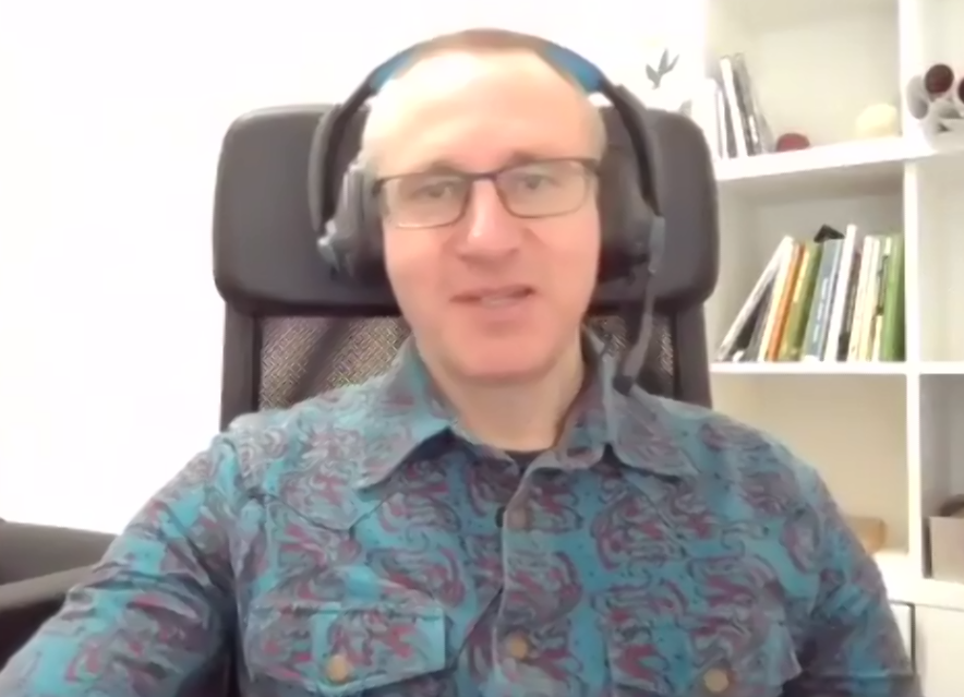 A man sits on a chair facing a screen on a zoom call. He is wearing a blue and purple shirt and headphones.