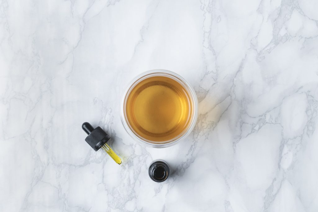 A marble counter top with a yellow glass cup of tea in it next to a brown CBD oil dropper and bottle